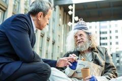 Ενθαρρυντικός ξένος που δίνει τα άστεγα χρήματα για τα τρόφιμα Στοκ Εικόνες
