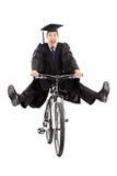 Ενθουσιασμένος απόφοιτος φοιτητής που οδηγά ένα ποδήλατο Στοκ εικόνα με δικαίωμα ελεύθερης χρήσης
