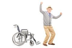 Ενθουσιασμένος πρεσβύτερος που στέκεται επάνω από μια αναπηρική καρέκλα Στοκ Φωτογραφία