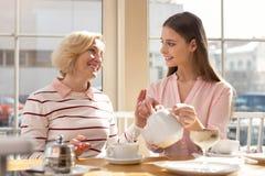 Ενθουσιώδης εγγονή που έχει το τσάι με τη γιαγιά της στοκ φωτογραφία με δικαίωμα ελεύθερης χρήσης