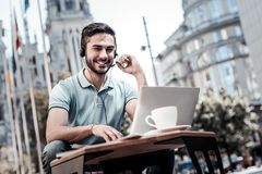 Ενθουσιώδης χιλιετής τύπος που έχει την επιχειρησιακή τηλεοπτική κλήση στο lap-top στοκ φωτογραφίες