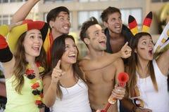 Ενθουσιώδεις γερμανικοί ανεμιστήρες αθλητικού ποδοσφαίρου που γιορτάζουν τη νίκη. Στοκ Εικόνα