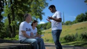 Ενθουσιώδεις εθελοντές που κάθονται στο πάρκο απόθεμα βίντεο
