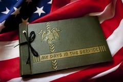 Ενθύμηση του παλαιμάχου ημέρας μνήμης με το λεύκωμα και τη σημαία στρατιωτικής υπηρεσίας. Στοκ Εικόνες