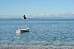 Ενιαία βάρκα κωπηλασίας μπροστά από διαμορφωμένο το πυραμίδα νησί Στοκ Φωτογραφίες