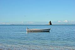 Ενιαία βάρκα κωπηλασίας μπροστά από διαμορφωμένο το πυραμίδα νησί Στοκ φωτογραφία με δικαίωμα ελεύθερης χρήσης