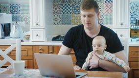 Ενιαίος μπαμπάς που εργάζεται σε έναν φορητό προσωπικό υπολογιστή με  φιλμ μικρού μήκους