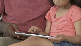 Ενιαίος πατέρας που εξηγεί στην κόρη πώς να χρησιμοποιήσει την ταμπλέτα, παίζοντας παιχνίδια, εργασία απόθεμα βίντεο