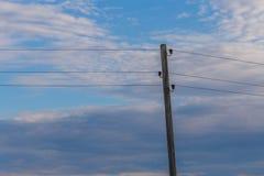 Ενιαίος πόλος ηλεκτρικής ενέργειας με τα καλώδια στο υπόβαθρο μπλε ουρανού Στοκ Εικόνα