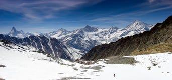 Ενιαίος backcountry σκιέρ σε ένα απέραντο τοπίο βουνών στο δρόμο του κάτω από μια υψηλή κορυφή με μια μεγάλη άποψη του Matterhorn Στοκ Εικόνες