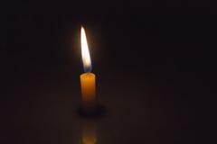 Ενιαίο απλά κερί αναμμένο στο σκοτεινό υπόβαθρο Στοκ εικόνα με δικαίωμα ελεύθερης χρήσης