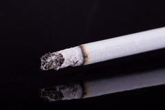 Ενιαίο καίγοντας τσιγάρο με την τέφρα που απομονώνεται στο μαύρο υπόβαθρο Στοκ φωτογραφίες με δικαίωμα ελεύθερης χρήσης