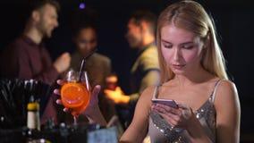 Ενιαίο κομψό θηλυκό χρησιμοποιώντας τηλέφωνο στη λέσχη νύχτας απόθεμα βίντεο