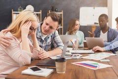 Ενισχυτική γυναίκα ανδρών που διαβάζει τις κακές ειδήσεις στο ηλεκτρονικό ταχυδρομείο Στοκ Εικόνες
