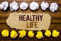 Εννοιολογική υγιής ζωή λέξης κειμένων χεριών Επιχειρησιακή έννοια για τα τρόφιμα καλών υγειών που γράφονται στην κολλώδη σημείωση στοκ εικόνα
