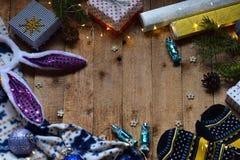 Εννοιολογική χειμερινή εικόνα Άνετο πλαίσιο Χριστουγέννων με τα δώρα, διακοσμήσεις Χριστουγέννων, γάντια, καραμέλα στο ξύλινο υπό Στοκ Εικόνες