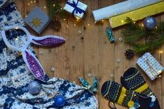 Εννοιολογική χειμερινή εικόνα Άνετο πλαίσιο Χριστουγέννων με τα δώρα, διακοσμήσεις Χριστουγέννων, γάντια, καραμέλα στο ξύλινο υπό Στοκ Εικόνα