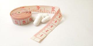 Εννοιολογικός μακρο, πλαστικός ρόδινος μετρητής ραφτών και άσπρα χάπια, απεικόνιση για τον έλεγχο φαρμάκων για τη συντήρηση υγιή  στοκ φωτογραφίες με δικαίωμα ελεύθερης χρήσης