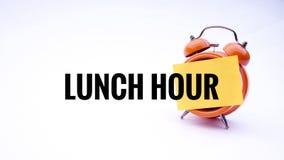 Εννοιολογική εικόνα της επιχειρησιακής έννοιας με την ώρα του μεσημεριανού λέξεων σε ένα ρολόι με ένα άσπρο υπόβαθρο Εκλεκτική εσ Στοκ εικόνες με δικαίωμα ελεύθερης χρήσης