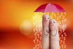Εννοιολογική τέχνη δάχτυλων Οι εραστές αγκαλιάζουν και κρατούν την ομπρέλα με τα μειωμένα λουλούδια νεολαίες γυναικών αποθεμάτων  Στοκ Εικόνα