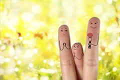 Εννοιολογική τέχνη οικογενειακών δάχτυλων Ο πατέρας και η κόρη δίνουν στα λουλούδια τη μητέρα του νεολαίες γυναικών αποθεμάτων πο Στοκ εικόνες με δικαίωμα ελεύθερης χρήσης