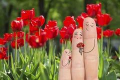 Εννοιολογική τέχνη οικογενειακών δάχτυλων Ο πατέρας και ο γιος δίνουν στα λουλούδια τη μητέρα του νεολαίες γυναικών αποθεμάτων πο Στοκ εικόνα με δικαίωμα ελεύθερης χρήσης