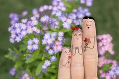 Εννοιολογική τέχνη οικογενειακών δάχτυλων Ο πατέρας και ο γιος δίνουν στα λουλούδια τη μητέρα του νεολαίες γυναικών αποθεμάτων πο Στοκ φωτογραφία με δικαίωμα ελεύθερης χρήσης