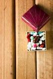 Εννοιολογικός της κάψας στο κιβώτιο δώρων στο ξύλινο υπόβαθρο Τοπ όψη Στοκ Φωτογραφία