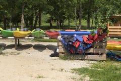 Ενοίκιο καγιάκ Τα χρωματισμένα καγιάκ που τοποθετούνται στα ράφια είναι στην παραλία Καπόκ και κουπιά που τακτοποιούνται σε ένα ξ στοκ φωτογραφία με δικαίωμα ελεύθερης χρήσης