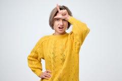 Ενοχλημένη γυναίκα που παρουσιάζει ηττημένος-σημάδι πέρα από το μέτωπο, που στέκεται με την ασέβεια στοκ φωτογραφία