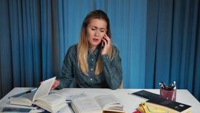Ενοχλημένη καιη γυναίκα σπουδαστής σε ένα πουκάμισο τζιν, που μιλά σε ένα smartphone η στιγμή όταν κάνει την εργασία αυτή απόθεμα βίντεο