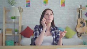 Ενοχλημένη νέα γυναίκα με τη διαθέσιμη ομιλία πιστωτικών καρτών στο τηλέφωνο σε ένα σύγχρονο διαμέρισμα απόθεμα βίντεο