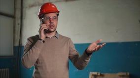 Ενοχλημένος μηχανικός που μιλά στο κινητό τηλέφωνο στην εργασία απόθεμα βίντεο