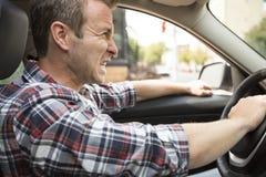 Ενοχλημένος νεαρός άνδρας που οδηγεί ένα αυτοκίνητο Ενοχλημένος οδηγός Στοκ εικόνα με δικαίωμα ελεύθερης χρήσης