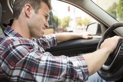 Ενοχλημένος νεαρός άνδρας που οδηγεί ένα αυτοκίνητο Ενοχλημένος οδηγός Στοκ φωτογραφία με δικαίωμα ελεύθερης χρήσης