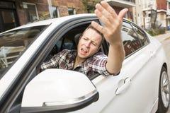 Ενοχλημένος νεαρός άνδρας που οδηγεί ένα αυτοκίνητο Ενοχλημένος οδηγός Στοκ Φωτογραφία