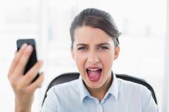 Ενοχλημένη αριστοκρατική καφετιά μαλλιαρή επιχειρηματίας που κραυγάζει κρατώντας ένα κινητό τηλέφωνο Στοκ φωτογραφία με δικαίωμα ελεύθερης χρήσης