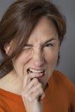 Ενοχλημένη όμορφη μέση ηλικίας γυναίκα που δαγκώνει το δάχτυλό της, κλείσιμο του ματιού Στοκ φωτογραφία με δικαίωμα ελεύθερης χρήσης