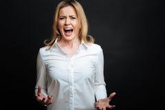 Ενοχλημένη ώριμη γυναίκα που φωνάζει στο στούντιο Στοκ Φωτογραφία