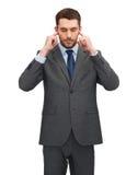 Ενοχλημένος επιχειρηματίας που καλύπτει τα αυτιά με τα χέρια του Στοκ Φωτογραφίες