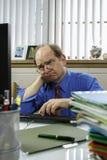 Ενοχλημένος επιχειρηματίας στο γραφείο που εξετάζει τον υπολογιστή, κάθετο Στοκ Φωτογραφία