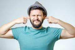 Ενοχλημένος νεαρός άνδρας που συνδέει τα αυτιά με τα χέρια Στοκ Εικόνες