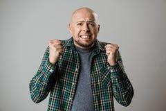 Ενοχλημένος νεαρός άνδρας που σφίγγει τις πυγμές του πέρα από το μπεζ υπόβαθρο Στοκ φωτογραφία με δικαίωμα ελεύθερης χρήσης