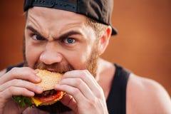 0 ενοχλημένος νεαρός άνδρας που τρώει το χάμπουργκερ υπαίθρια Στοκ Εικόνα