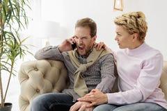 Ενοχλημένος τύπος που μιλά στο smartphone κοντά στη σύζυγό του Στοκ Εικόνες