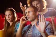 Ενοχλητικό άτομο στο τηλέφωνο κατά τη διάρκεια του κινηματογράφου Στοκ εικόνα με δικαίωμα ελεύθερης χρήσης