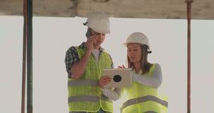 Ενσωματώνοντας την κατασκευή με ένα θηλυκό και αρσενικοί οικοδόμοι, κατασκευαστές, μηχανικοί που περπατούν κατά μήκος του απόθεμα βίντεο