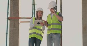 Ενσωματώνοντας την οικοδόμηση με έναν θηλυκό και αρσενικοί μηχανικοί που χρησιμοποιούν μια ταμπλέτα και ένα κινητό τηλέφωνο για ν απόθεμα βίντεο