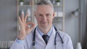 Εντάξει σημάδι από το θετικό γιατρό με τις γκρίζες τρίχες απόθεμα βίντεο