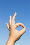 Εντάξει σημάδι χεριών στο υπόβαθρο ουρανού Στοκ Εικόνα